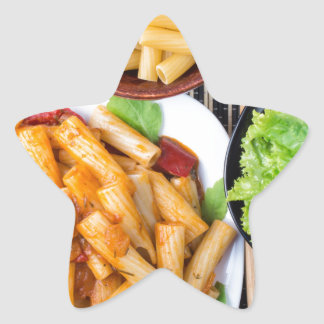 Top view of cooked rigatoni pasta with vegetables star sticker