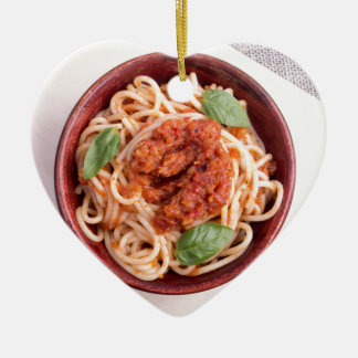 Top view of cooked spaghetti with tomato relish ceramic heart ornament