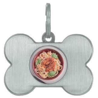Top view of cooked spaghetti with tomato relish pet name tag