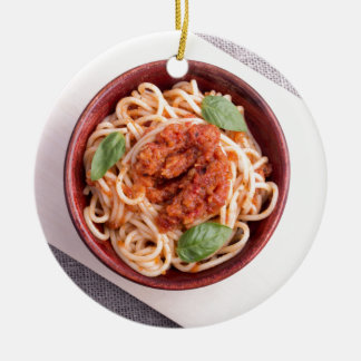 Top view of cooked spaghetti with tomato relish round ceramic ornament