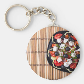 Top view of fresh vegetarian salad on a black basic round button keychain