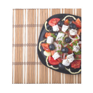 Top view of fresh vegetarian salad on a black notepads
