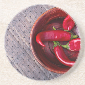 Top view of hot red chili peppers in a brown wood beverage coaster