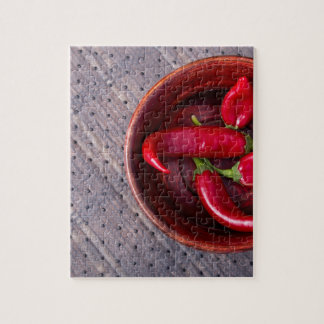 Top view of hot red chili peppers in a brown wood jigsaw puzzle