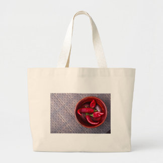 Top view of hot red chili peppers in a brown wood large tote bag