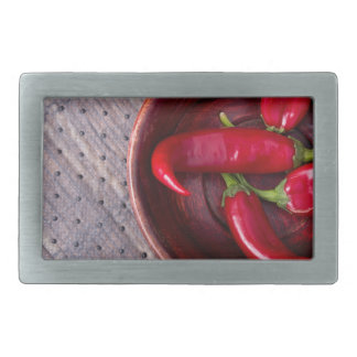 Top view of hot red chili peppers in a brown wood rectangular belt buckle
