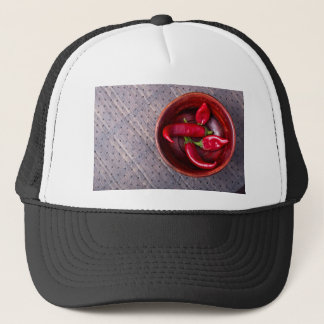 Top view of hot red chili peppers in a brown wood trucker hat