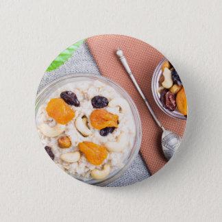 Top view of oatmeal porridge with raisins, cashews 2 inch round button