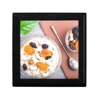 Top view of oatmeal porridge with raisins, cashews gift box