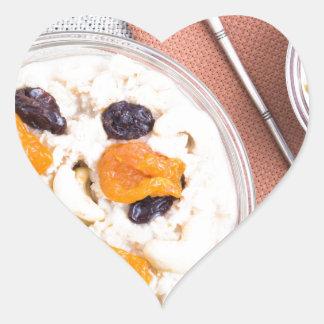 Top view of oatmeal porridge with raisins, cashews heart sticker