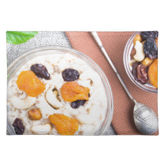 Top view of oatmeal porridge with raisins, cashews placemat