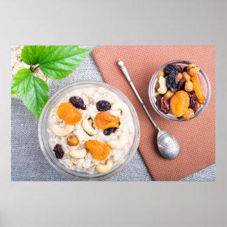 Top view of oatmeal porridge with raisins, cashews poster