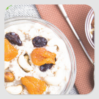 Top view of oatmeal porridge with raisins, cashews square sticker