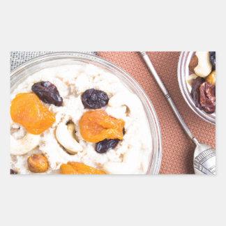 Top view of oatmeal porridge with raisins, cashews sticker