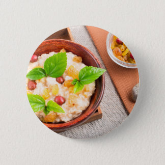 Top view of oatmeal with raisins, berries and herb 2 inch round button