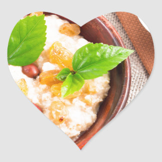 Top view of oatmeal with raisins, berries and herb heart sticker