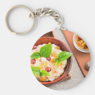 Top view of oatmeal with raisins, berries and herb keychain