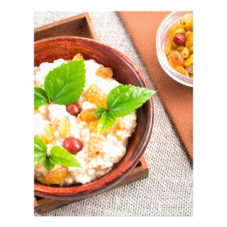 Top view of oatmeal with raisins, berries and herb letterhead