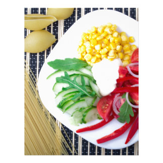 Top view of the vegetarian dish of raw vegetables letterhead