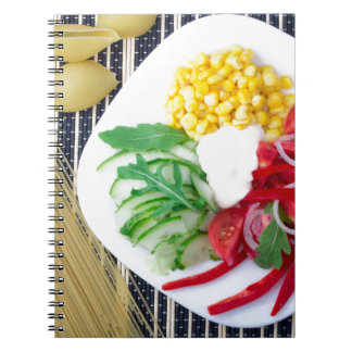 Top view of the vegetarian dish of raw vegetables notebook