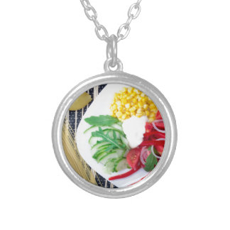 Top view of the vegetarian dish of raw vegetables silver plated necklace