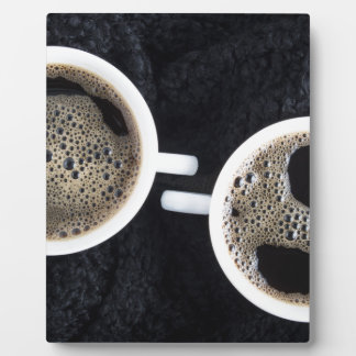 Top view of two small cups of coffee plaque
