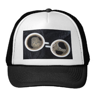 Top view of two small cups of coffee trucker hat