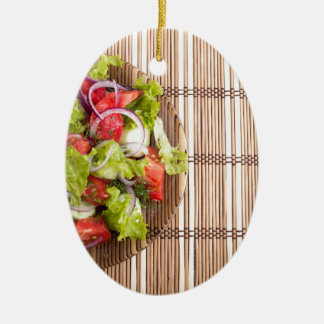 Top view of vegetarian salad from fresh vegetables ceramic oval ornament