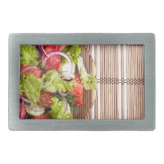 Top view of vegetarian salad from fresh vegetables rectangular belt buckles