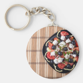 Top view of vegetarian salad in a black plate basic round button keychain