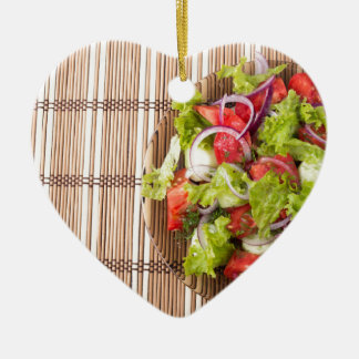 Top view of vegetarian salad on a bamboo mat ceramic heart ornament