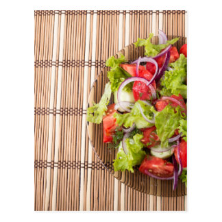 Top view of vegetarian salad on a bamboo mat postcard