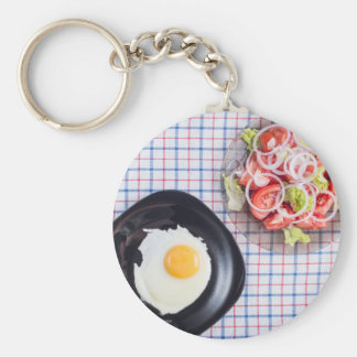 Top view on a black plate with a fried egg basic round button keychain