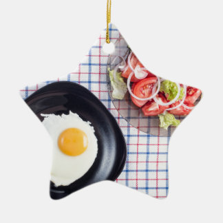 Top view on a black plate with a fried egg ceramic star ornament