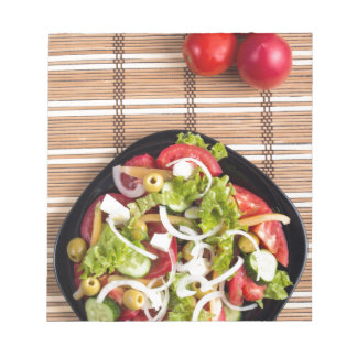 Top view on a fresh vegetable salad with natural notepad