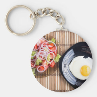 Top view on a fried egg and a salad of tomato basic round button keychain