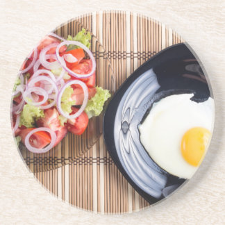 Top view on a fried egg and a salad of tomato beverage coaster