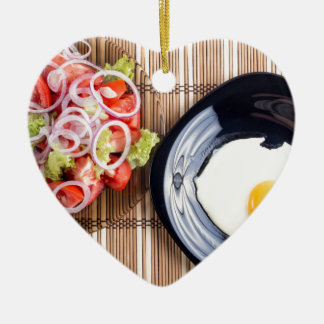 Top view on a fried egg and a salad of tomato ceramic heart ornament