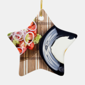Top view on a fried egg and a salad of tomato ceramic star ornament