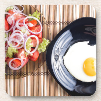 Top view on a fried egg and a salad of tomato coasters