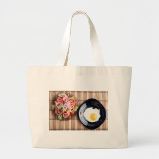 Top view on a fried egg and a salad of tomato large tote bag