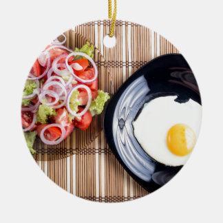 Top view on a fried egg and a salad of tomato round ceramic ornament