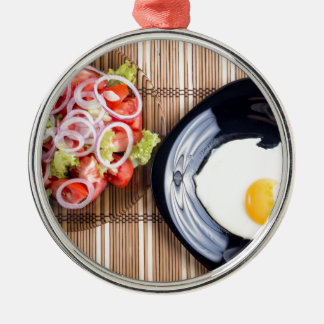 Top view on a fried egg and a salad of tomato Silver-Colored round ornament