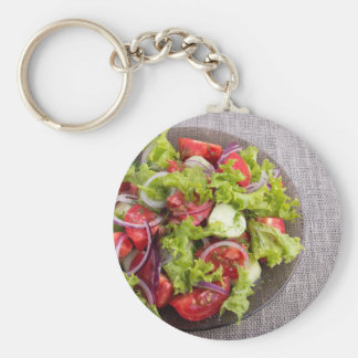 Top view on a plate with fresh salad of raw vegeta basic round button keychain