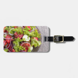 Top view on a plate with fresh salad of raw vegeta luggage tag