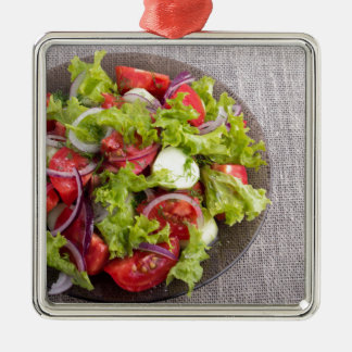Top view on a plate with fresh salad of raw vegeta Silver-Colored square ornament