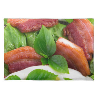 Top view on egg yolk, fried bacon and herbs placemats