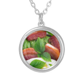 Top view on egg yolk, fried bacon and herbs silver plated necklace