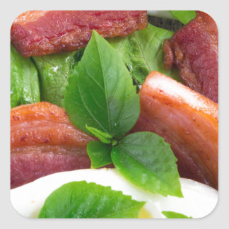 Top view on egg yolk, fried bacon and herbs square sticker