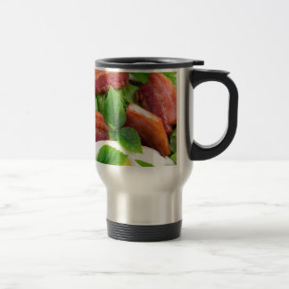 Top view on egg yolk, fried bacon and herbs travel mug